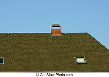 part of the roof of a private house made of green tiles with one brown brick chimney