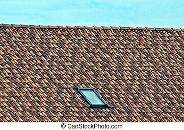 part of the roof with a colored tiled surface and a small window on the sky background