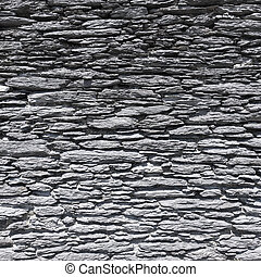 very old wall made of flat natural stones in ireland