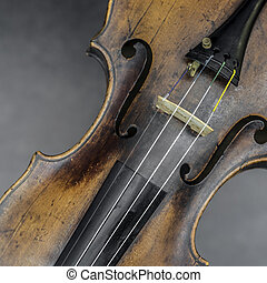 part of violin with f hole against gray background