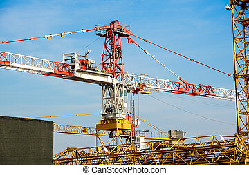 Part of yellow construction tower crane arm against blue sky