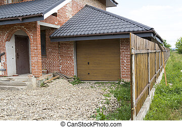 Part view of modern two-storied not finished new brick family cottage house with steep brown shingled roof, attached garage, temporary wooden fence. Construction, investment, real property concept.