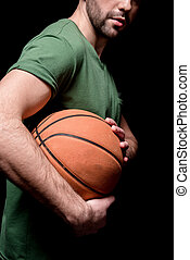partial side view of man holding basketball ball in hands