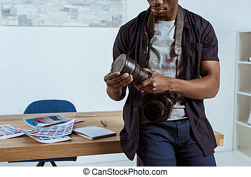 partial view of african american photographer with photo camera