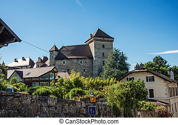 Partial view of Annecy Castle and houses with a wall in foreground and blue sky at Annecy.