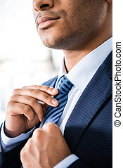 partial view of elegant businessman in suit tying necktie