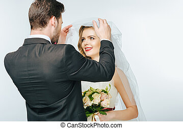 partial view of groom looking at beautiful bride in veil with bouquet of flowers