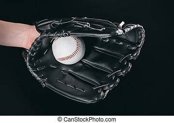 partial view of hand in glove holding baseball ball isolated on black