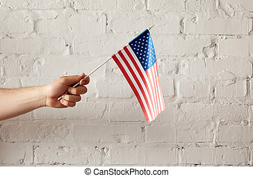 partial view of man holding american flagpole against white brick wall