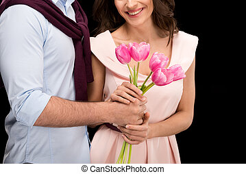 partial view of man presenting tulips bouquet to smiling woman on black