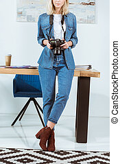 partial view of photographer with photo camera in hands leaning on table in studio
