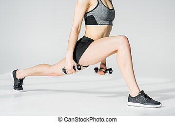Partial view of young athletic woman training with dumbbells