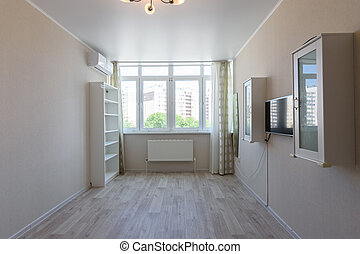 Partially empty room in the apartment with large windows