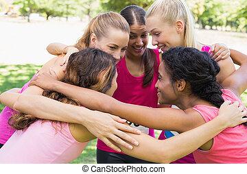 Participants of breast cancer marathon forming huddle