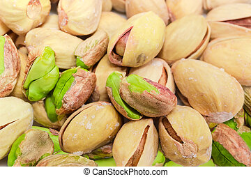 Partly peeled roasted salted pistachio nuts closeup at selective focus
