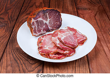 Partly sliced dried pork neck on dish on rustic table