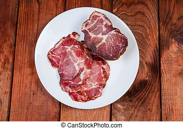 Partly sliced dried pork neck on white dish, top view