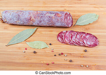 Partly sliced dry-cured sausage among spices on cutting board