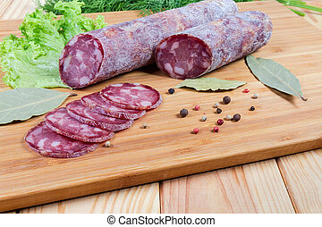 Partly sliced dry-cured sausage, greens, spices on cutting board
