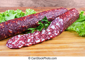 Partly sliced dry-cured sausages with lettuce on cutting board