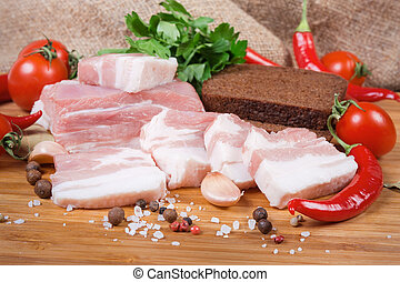 Partly sliced pork belly among spices, closeup in selective focus