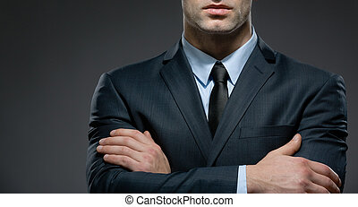 Partly viewed man wearing business suit and black tie with arms crossed