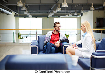 Partners interacting - Two business people interacting while...