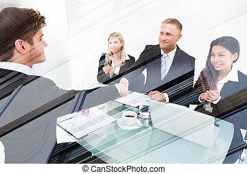 Partners Shaking Hands At Desk