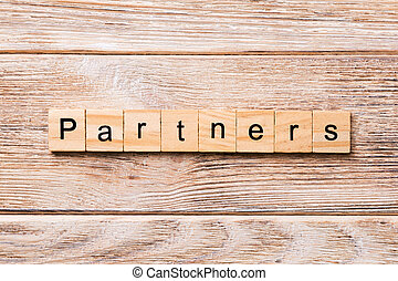 Partners word written on wood block. Partners text on wooden table for your desing, concept