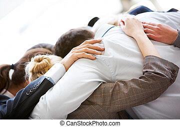 Partnership embrace - Circle of business people embracing...