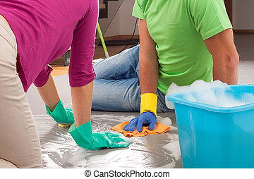Partnership in housework - Couple clean up their house in...
