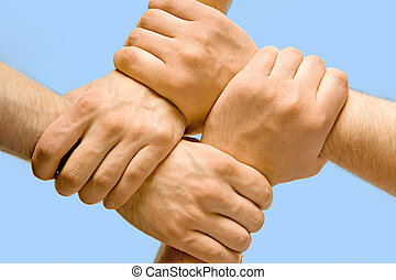 Partnership - Image of crossed hands isolated over blue...