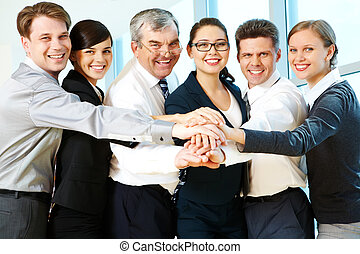Partnership - Row of smiling co-workers making pile of hands...