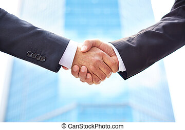 Partnership - Close-up of business partners shaking hands to...