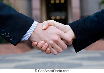 partnership - two hands in formal attire shaking on a deal