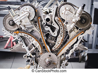 Parts of a disassembled car engine organised on the table for the period of repair