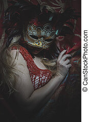 Party, Blonde with gold mask on red cloth embroidered golden thread, mystery and sensuality