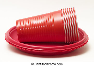 Stack of red plastic cups over disposable plates
