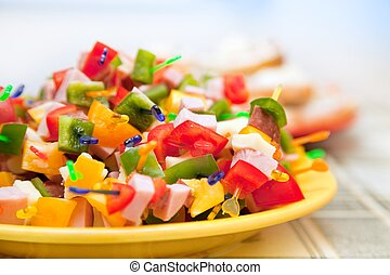 Party food, ham, salami cheese and vegetables on plastic sticks