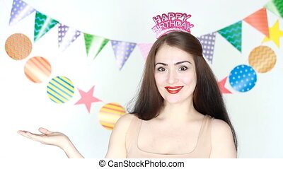 Party. Happy birthday. Decor for celebration. The funny girl smiles and show hand copyspace . Portrait of a young happy woman close-up