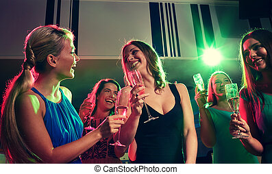 young women with glasses of champagne in club - party,...