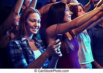 woman with smartphone texting message at concert - party, ...