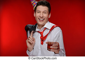 Party man. Drunk businessman in party hat standing with a glass of whiskey while isolated on red