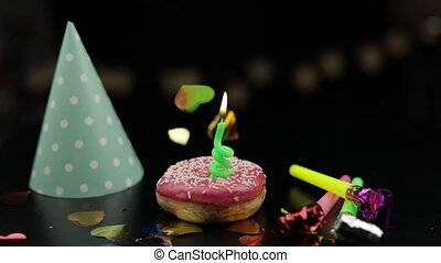 Party. Pink donut and a red festive candle on it. Golden confetti fall