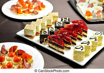 Party table with cakes and canapes - Food on the indoor...
