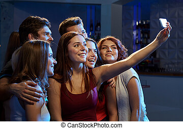 friends with smartphone taking selfie in club - party, ...
