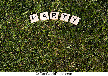 Party written in tiles on green grass