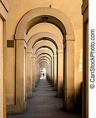 Passageway in Florence with round arches and person at the end