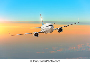 Passanger airplane above the clouds horizon sky with bright sunset colors.