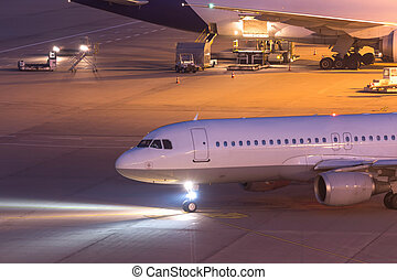 passenger aiplane moving on an airport at night